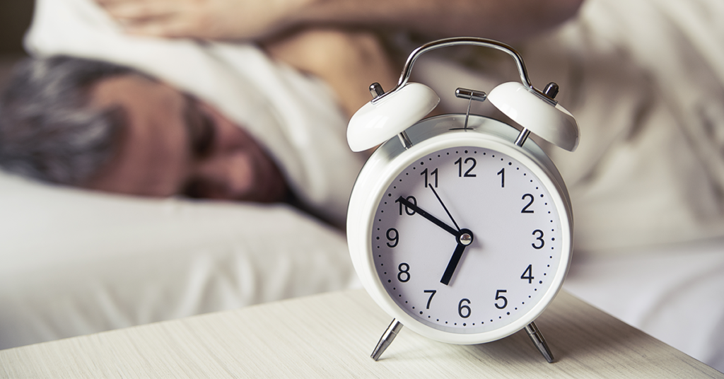Man covering his ears with a pillow when his alarm goes off in the morning