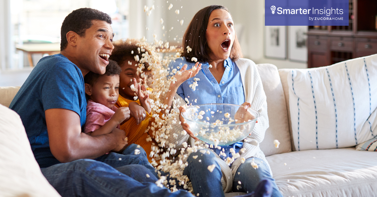 Family spills popcorn while watching TV on the couch