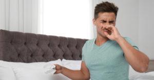 Man sneezing from allergies in his bedroom