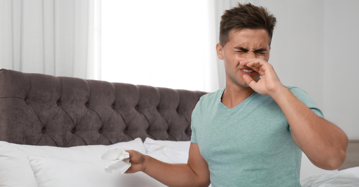 Man sneezing from allergies in his bedroom