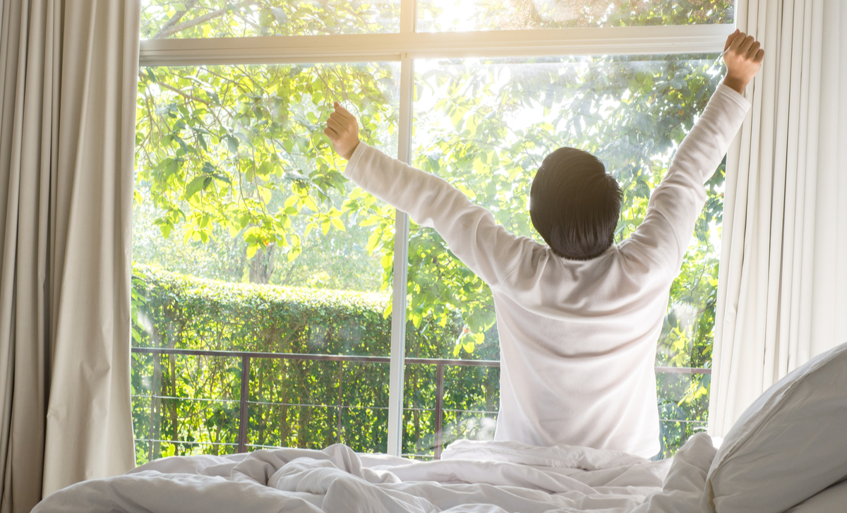 Man stretches his arms as he sits on his bed and wakes to a beautiful sunny day